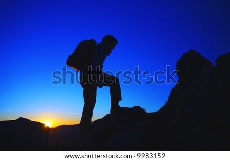 Rock climber ascending the mountain - stock photo