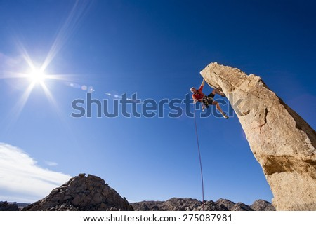Rock climber asscends a rock spire in Joshua Tree National Park. - stock photo