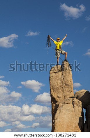 Rock climber balances on the summit after a successful and challenging ascent. - stock photo