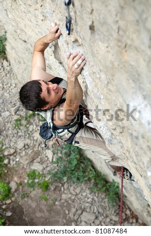 Rock climber battling his way up - stock photo