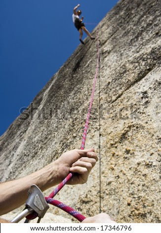 Rock climber being lowered by his partner with  their safety rope in Yosemite National Park, California, on a summer day. - stock photo