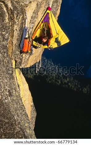Rock climber bivouacked in his portaledge on an overhanging cliff. - stock photo