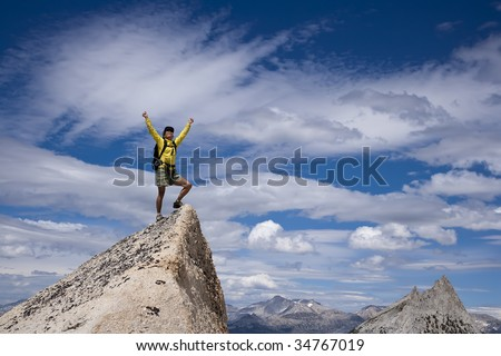 Rock climber celebrates  on the needle pointed summit of a pinnacle after a successful ascent. - stock photo
