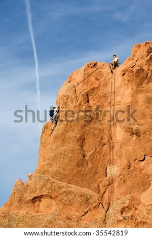 Rock climber climbing a cliff - stock photo