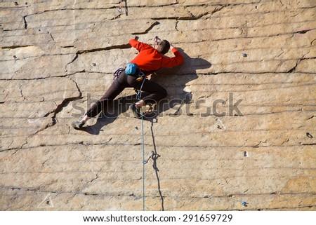 rock climber climbing an overhanging cliff - stock photo