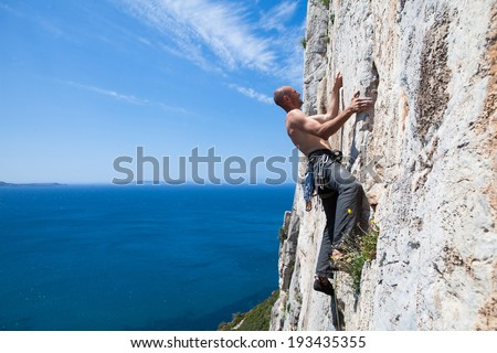 Rock climber climbing on the cliffs of Masua, west coast of Sardinia, Italy