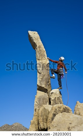 Rock climber clinging to the edge of a pinnacle.