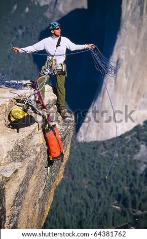 Rock climber coils ropes on the summit after a successful ascent. - stock photo