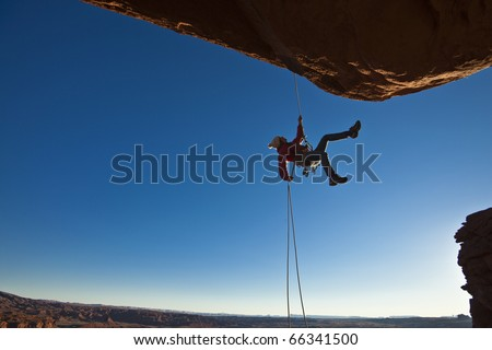 Rock climber dangles in midair as she  rappells past an overhang. - stock photo