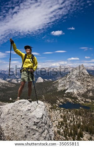 Rock climber enjoys the view from the summit of a pinnacle after a successful ascent. - stock photo