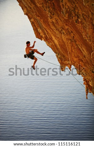 Rock climber falling of a cliff while lead climbing - stock photo
