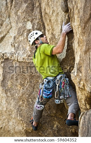 Rock climber grips a crack and prepares for his next move, in Joshua Tree National Park, California.