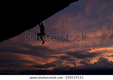 Rock climber hanging off overhanging cliff with a nice sunset background