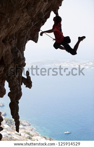 Rock climber jumping on next handhold, Kalymnos Island, Greece - stock photo