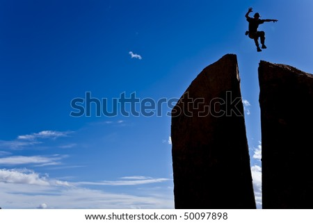 Rock climber leaps across a gap on the summit of a split spire.