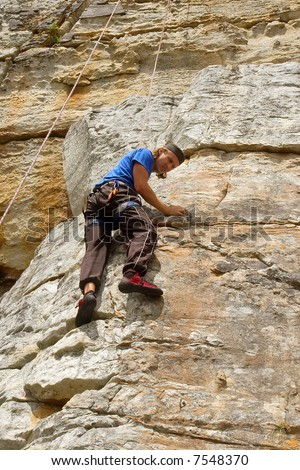 Rock climber looks down. Shot in Silvermine nature reserve, near Table Mountain National Park, Cape Town, South Africa.