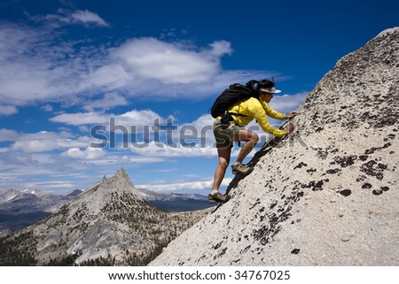 Rock climber make her final moves onto the summit of a pinnacle  as storm clouds build in the distance. - stock photo