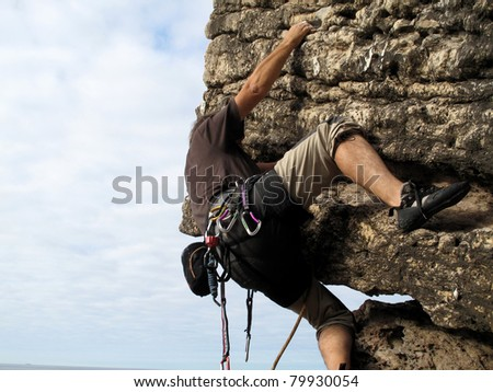 Rock climber on a cliff practicing traditional rock climbing - stock photo