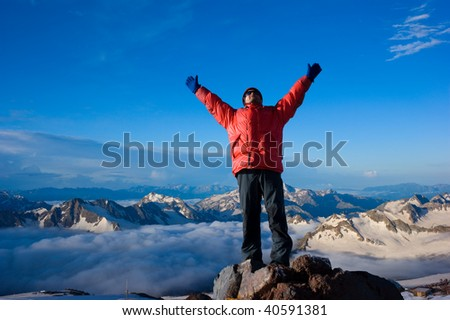 Rock-climber on background mountain landscape with the hands stretched in sides - stock photo