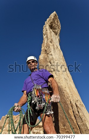 Rock climber on the summit after a successful ascent of a pinnacle.