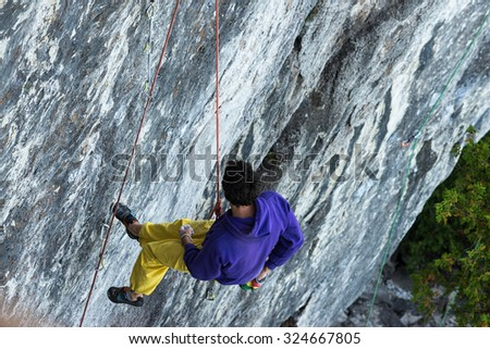 Rock Climber rappelling down a vertical cliff - stock photo