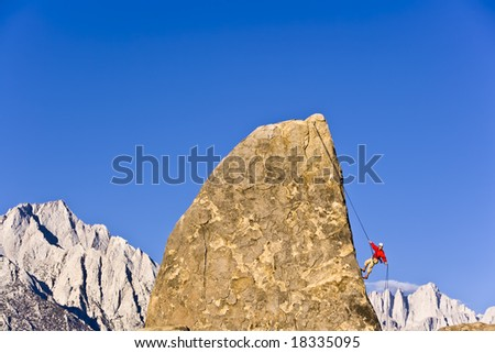 Rock climber rappelling from the summit of a rock spire below Mt. Whitney, California, on a sunny day. - stock photo