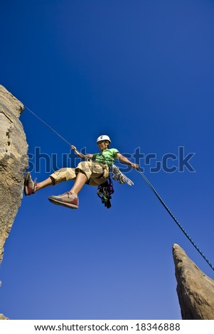 Rock climber rappelling from the summit of a rock spire in the Sierra Nevada Mountains, California, on a sunny day. - stock photo