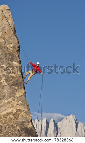 Rock climber rappels from the summit after a successful ascent. - stock photo