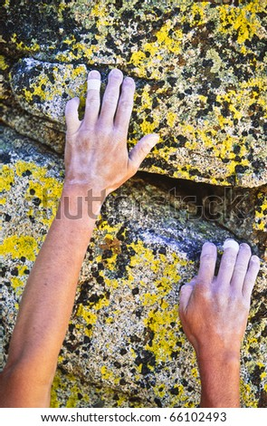 Rock climber reaching for the next hand hold on a steep wall. - stock photo