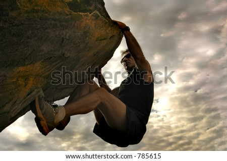 Rock climber reaching for the sky. - stock photo