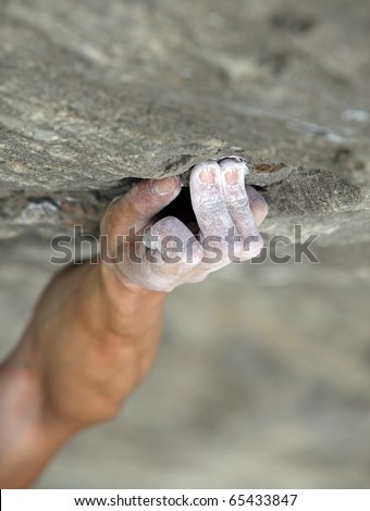 Rock climber's hand grasping handhold on natural cliff. His hand is covered in chalk. Shallow depth of field. - stock photo
