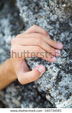 Rock climber's hand grasping handhold on natural cliff. Shallow depth of field. - stock photo