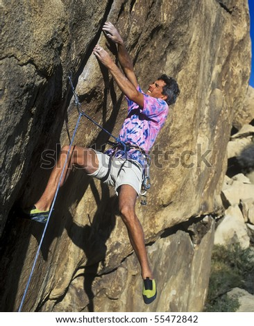 Rock climber scales a steep crack. - stock photo