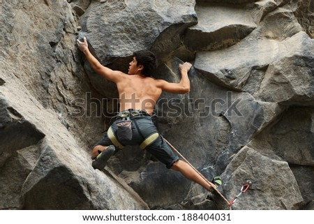 Rock climber searching for a connecting spot - stock photo