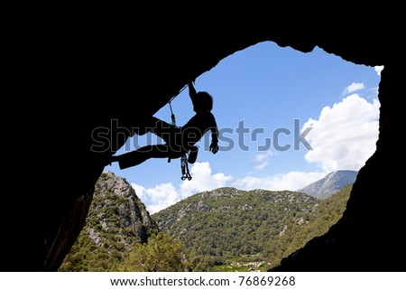 Rock climber silhouette in a sunny day climbing high - stock photo