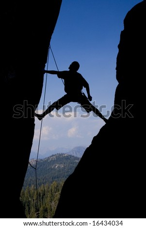 Rock climber stretching across a chimney.