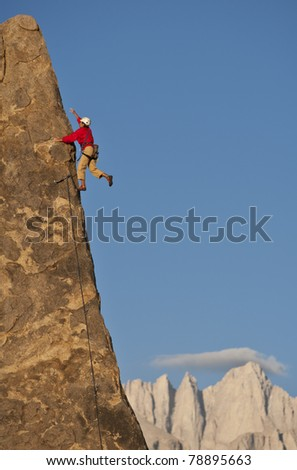 Rock climber struggles for her next grip on a challenging ascent. - stock photo