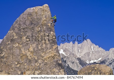 Rock climber struggles for his next grip on a challenging ascent. - stock photo