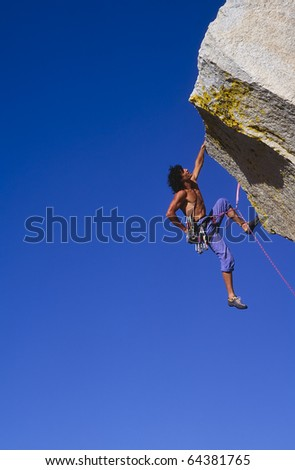 Rock climber struggles for his next grip on a overhanging cliff. - stock photo