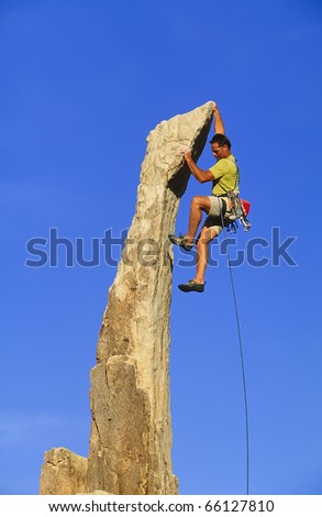 Rock climber struggles for his next grip on a overhanging pinnacle. - stock photo