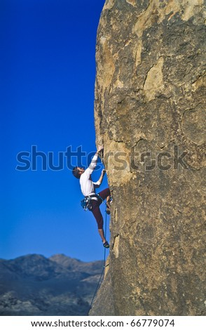 Rock climber struggles for his next grip on a overhanging pinnacle.