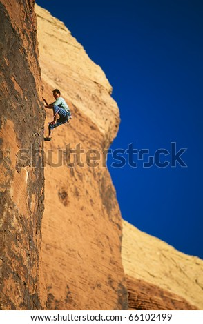 Rock climber struggles for his next grip on a sandstone cliff.
