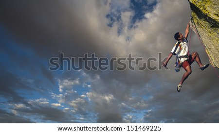 Rock climber struggles to the summit of a challenging pinnacle as storm clouds build behind him. - stock photo