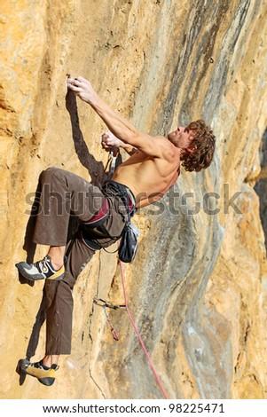 Rock climber struggling to take next handhold - stock photo