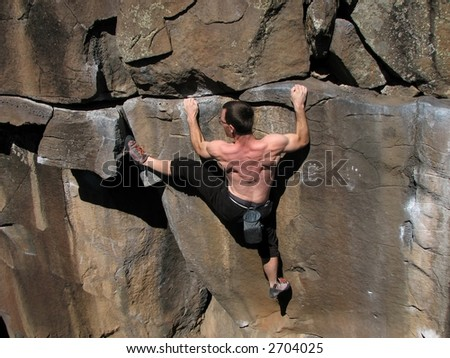 Rock climber without a rope strains to climb a cliff - stock photo