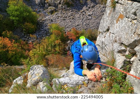 Rock climber woman gripping hand holds on steep limestone route - stock photo