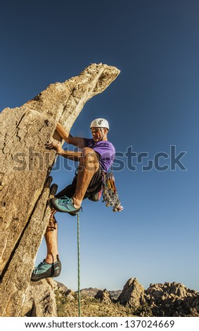 Rock climbers struggles for his next grip on a challenging ascent. - stock photo