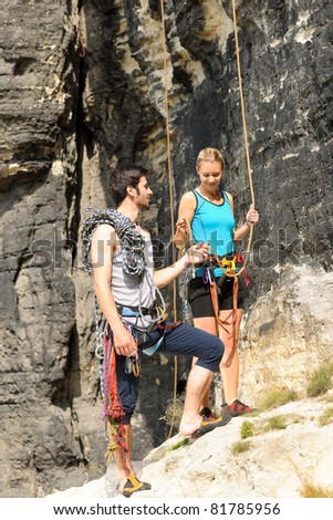 Rock climbing active young man showing mountaineer woman rope - stock photo