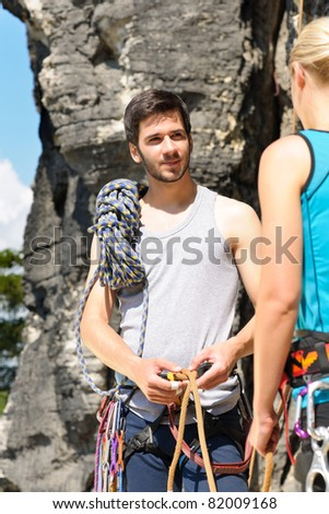Rock climbing active young man showing mountaineer woman rope knot - stock photo
