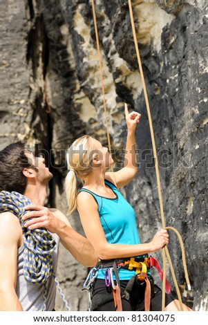 Rock climbing active young mountaineer people looking pointing up rope - stock photo